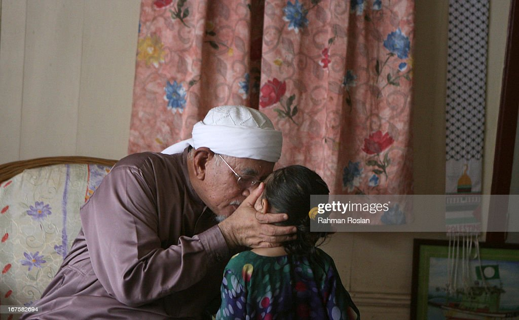 Abdul Hadi Awang, president of the Malaysian Pan Islamic Party, kisses his grand daughter at his home on April 26, 2013 in Rusila, Malaysia. Malaysia's 13th general election will be held on May 5.