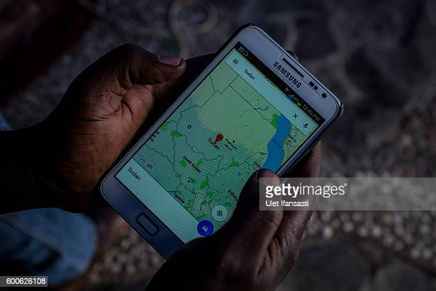 Abdul Hamid a refugee from Sudan displays a map of Sudan on his smartphone inside a temporary tent in the city park next to the regional parliament...
