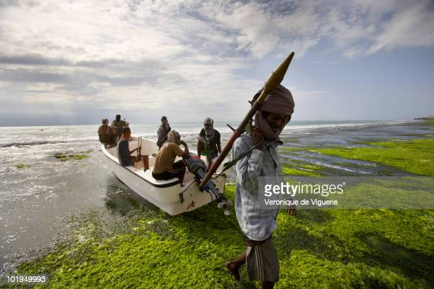Abdul Hassan carries an RPG near a small boat with some of his crew He is nicknamed 'the one who never sleeps' and is a chief of the pirate group...