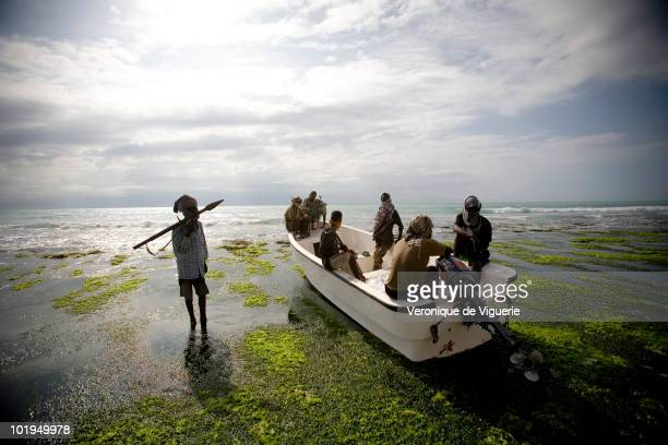 Abdul Hassan carries an RPG to a small boat with some of his crew He is nicknamed 'the one who never sleeps' and is a chief of the pirate group...