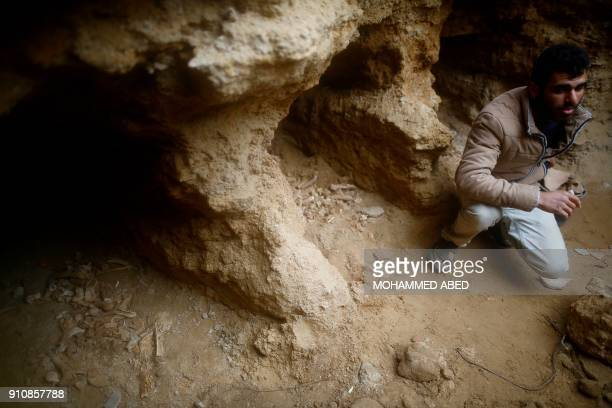 Abdul Karim alKafarnah a Palestinian resident of Beit Hanun collects pottery fragments at a freshlydiscovered cemetery in the garden of his house in...