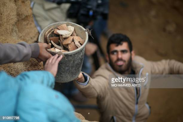 Abdul Karim alKafarnah a Palestinian resident of Beit Hanun passes on a bucket full of pottery fragments at a freshlydiscovered cemetery in the...