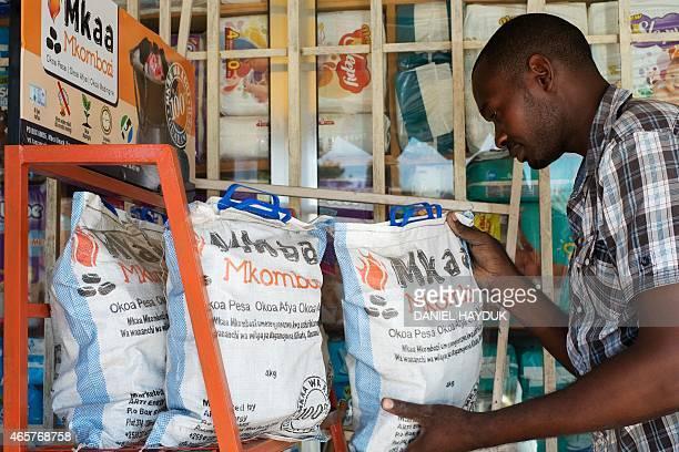 Abdul Karim Muhumbo stocks environmentally friendly charcoal at his shop in Dar es Salaam on March 10 2015 ARTI Energy is a Tanzanian company...
