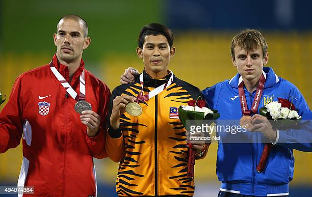 Abdul Latif Romly of Malaysia celebrates winning gold Zoran Talic of Croatia silver and Dmytro Prudnikov of Ukraine bronze after the men's long jump...