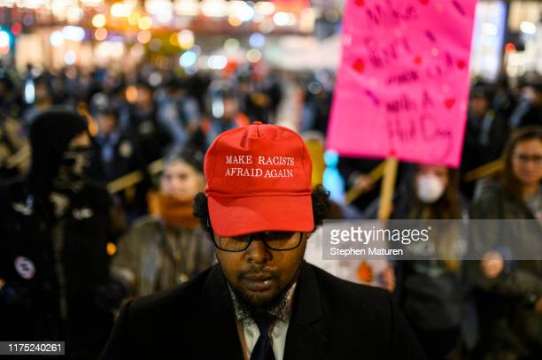 Abdul Mohmed stands with a group of protestors after a campaign rally for U.S. President Donald Trump at the Target Center on October 10, 2019 in...