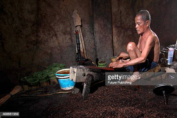 Abdul Muis cuts tobacco in traditional tobacco curing factory on April 6. 2015 in Makassar, Indonesia. PHOTOGRAPH BY Jefta Images / Barcroft Media