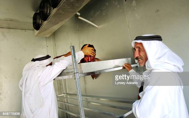 Abdul Munim Ali Hamood left joined by his brother looks at the face of his only son in the morgue at the Al Karama Hospital after he was killed in...