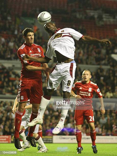 Abdul Osman of Northampton Town heads the ball under pressure from Martin Kelly of Liverpool during the Carling Cup Third Round match between...