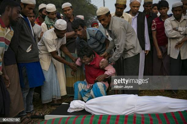 COX'S BAZAR BANGLADESH JANUARY 12 Abdul Rahim cries over the bodies of his wife and children before their burial in Balukhali camp on January 12 2018...