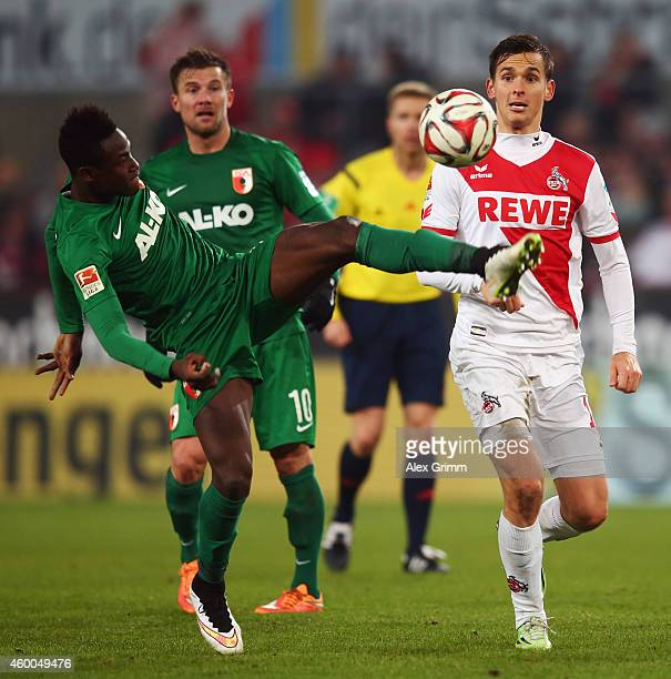 Abdul Rahman Baba of Augsburg clears the ball ahead of Pawel Olkowski of Koeln during the Bundesliga match between 1 FC Koeln and FC Augsburg at...
