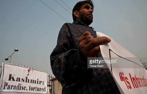Abdul Rashid a former militant and torture victim holds a banner with his amputated fingers on December 9 2012 in Srinagar the summer capital of...