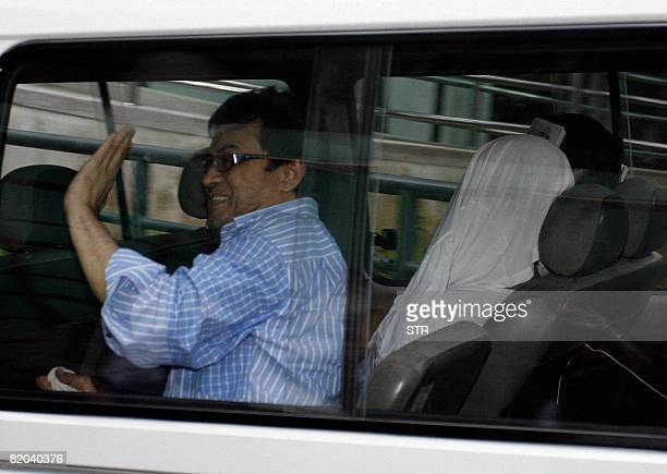 Abdul Razak Baginda a close friend of Deputy Prime Minister Najib Razak waves to his family member as he arrives at Shah Alam High Court on July 23...