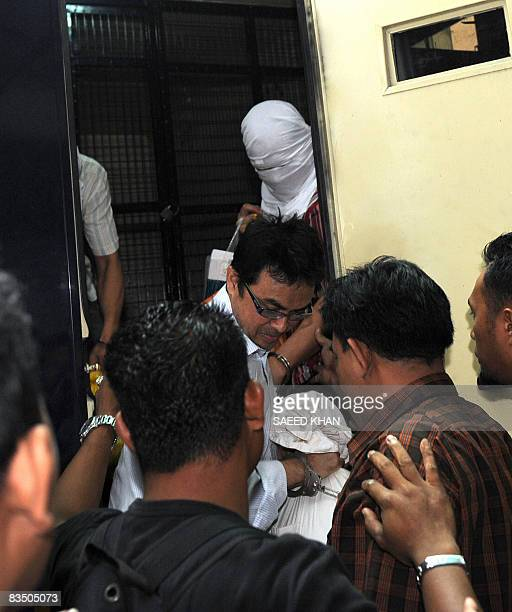Abdul Razak Baginda a highprofile political analyst alights from a correctional services vehicle carrying defendants in Shah Alam west of Kuala...