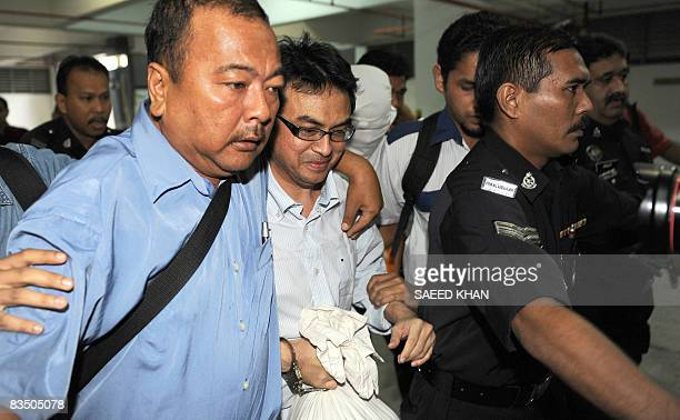 Abdul Razak Baginda a highprofile political analyst walks towards the court room in police custody in Shah Alam west of Kuala Lumpur on October 31...