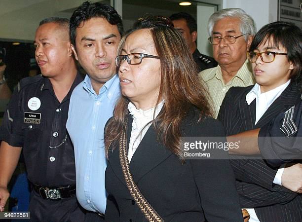 Abdul Razak Baginda executive director at Malaysian Strategic Research Centre second from left is led to lock up at Shah Alam Court in Selangor...