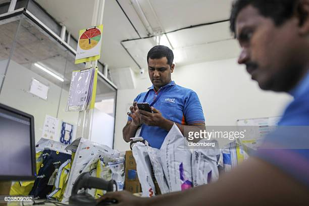 Abdul Saleem a deliveryman known as a Wishmaster for Flipkart Online Services Pvt's Ekart Logistics service uses a smartphone at the company's office...
