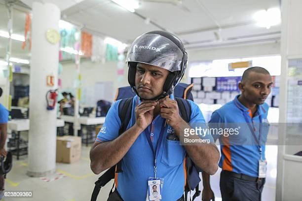 Abdul Saleem a deliveryman known as a Wishmaster for Flipkart Online Services Pvt's Ekart Logistics service center puts on a helmet as he prepares to...