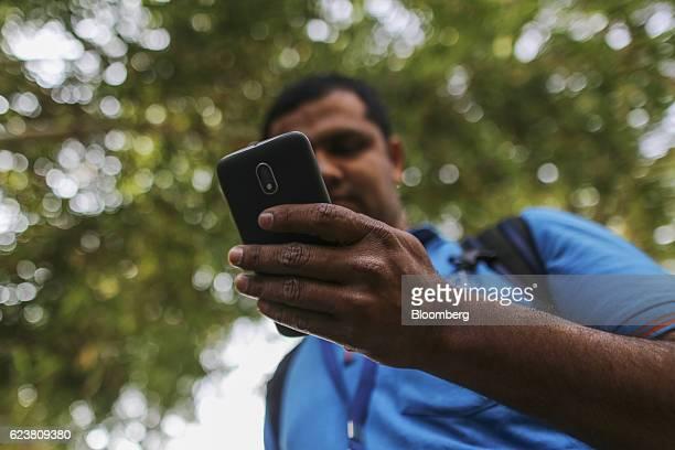 Abdul Saleem a deliveryman known as a Wishmaster for Flipkart Online Services Pvt's Ekart Logistics service uses a smartphone while delivering...