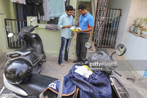 Abdul Saleem a deliveryman known as a Wishmaster for Flipkart Online Services Pvt's Ekart Logistics service right delivers a package to a customer in...