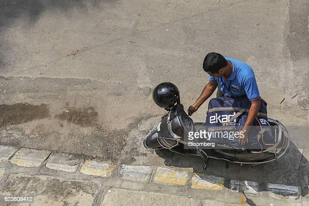 Abdul Saleem a deliveryman known as a Wishmaster for Flipkart Online Services Pvt's Ekart Logistics service arranges a bag on a motorcycle in...