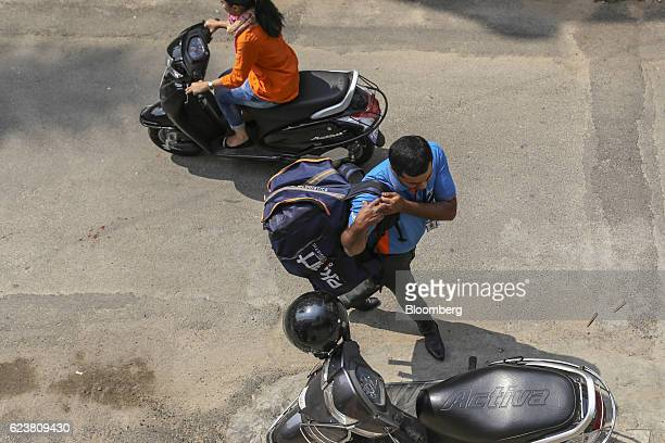 Abdul Saleem a deliveryman known as a Wishmaster for Flipkart Online Services Pvt's Ekart Logistics service carries a bag towards his motorcycle in...
