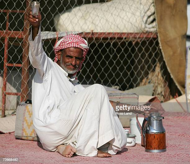 Abdula from the Sudan offers a cup of chai at the Al Mamura camel souq on November 29 2006 in Doha Qatar Camels are priced depending on weight age...