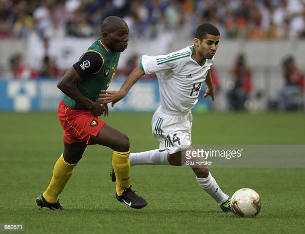 Abdulaziz al Khathran of Saudi Arabia looks to go past Geremi of Cameroon during the FIFA World Cup Finals 2002 Group E match played at the Saitama...