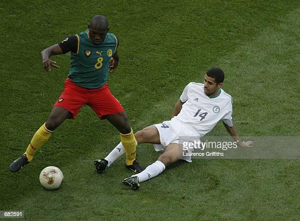Abdulaziz al Khathran of Saudi Arabia tries to tackle Geremi of Cameroon during the FIFA World Cup Finals 2002 Group E match played at the Saitama...
