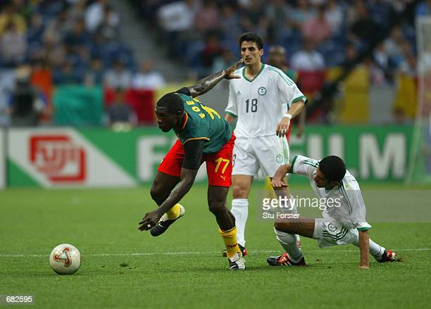 Abdulaziz Al Khathran of Saudi Arabia tries to tackle MarcVivien Foe of Cameroon during the FIFA World Cup Finals 2002 Group E match played at the...