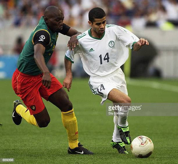 Abdulaziz Khathran of Saudi Arabia takes the ball past Geremi of Cameroon during the FIFA World Cup Finals 2002 Group E match played at the Saitama...