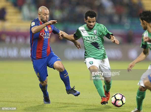 Abdulfattah Asiri of Al-Ahli Saudi FC in action against Javier Mascherano of Barcelona during the Qatar Airways Cup match between FC Barcelona and...