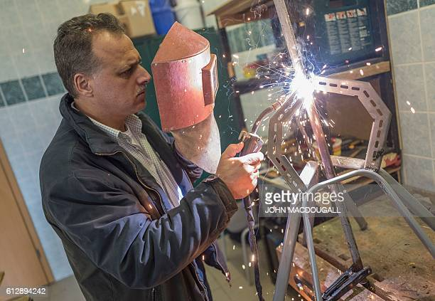 Abdulhadi Barnjakji a refugee from Damascus Syria solders pieces of scrap metal as he attends a workshop at Biotec a local association that provides...