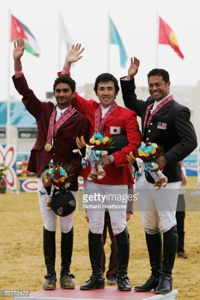 Abdulla Ali Abdulla al Ejail of Qatar Yoshiaki Oiwa of Japan Husref Malek Jeremiah of Malaysia stand on the podium after the Equestrian Individual...
