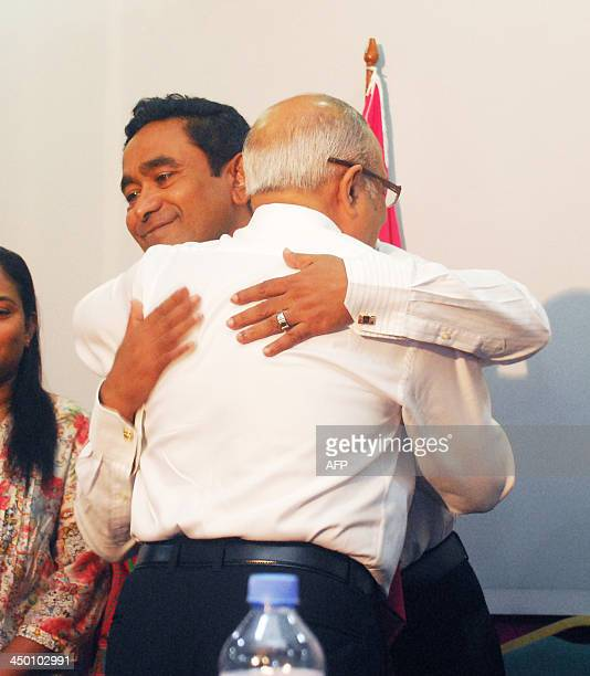 Abdulla Yameen smiles as he is hugged by an unidentified party official during a press conference at a local hotel in Male early on November 17 2013...