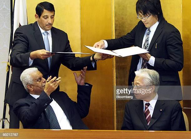Abdullah bin Hamad alAttiyah Qatar's deputy prime minister and minister of energy and industry left and Masayuki Naoshima Japan's minister for...