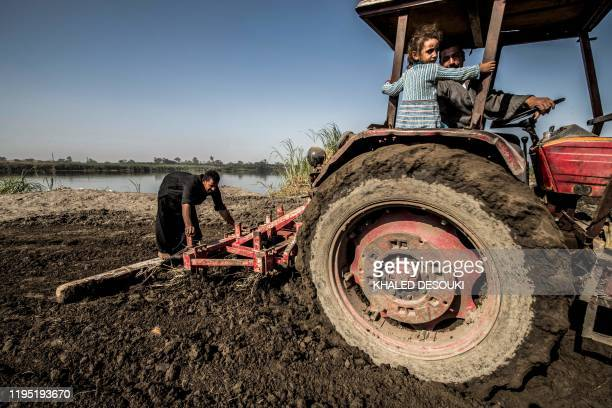 Abdullah elHity a 28yearold farmer drives a tractor as his 4yearold daughter Rodayna sits beside him while ploughing his field along the bank of the...