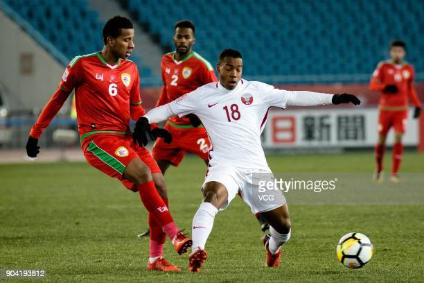 Abdullah Fawaz of Oman and Assim Madibo of Qatar compete for the ball during the AFC U23 Championship Group A match between Oman and Qatar at...