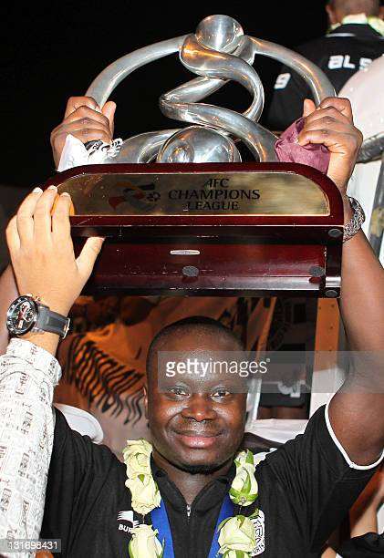 Abdullah Koni of Qatar's AlSadd club holds the winner's trophy upon the team's arrival at Doha airport on November 6 2011 after winning the AFC...