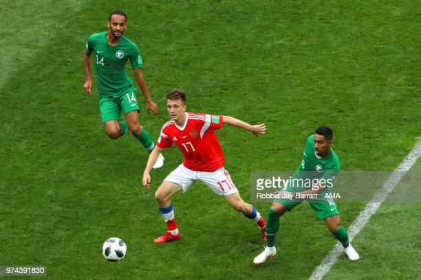 Abdullah Otayf and Salem Aldawsari of Saudi Arabia compete with Aleksandr Golovin of Russia during the 2018 FIFA World Cup Russia group A match...
