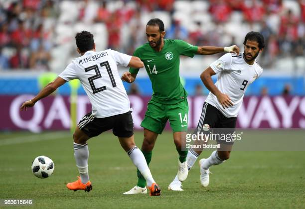 Abdullah Otayf of Saudi Arabia is challenged by Trezeguet of Egypt and Marwan Mohsen of Egypt during the 2018 FIFA World Cup Russia group A match...