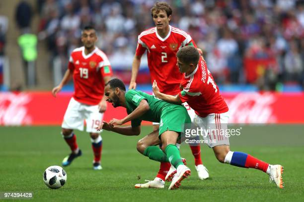 Abdullah Otayf of Saudi Arabia is tackled by Roman Zobnin of Russia during the 2018 FIFA World Cup Russia Group A match between Russia and Saudi...