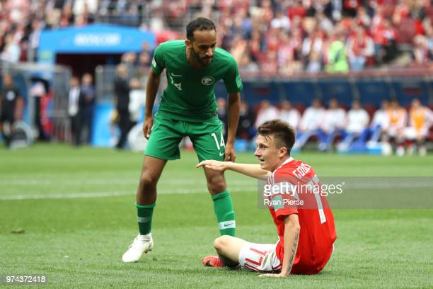 Abdullah Otayf of Saudi Arabia talks with Aleksandr Golovin of Russia after he goes down in the area during the 2018 FIFA World Cup Russia Group A...