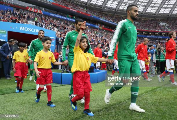 Abdullah Otayf of Saudi Arabia walks out to the pitch with his mascot prior to the 2018 FIFA World Cup Russia Group A match between Russia and Saudi...