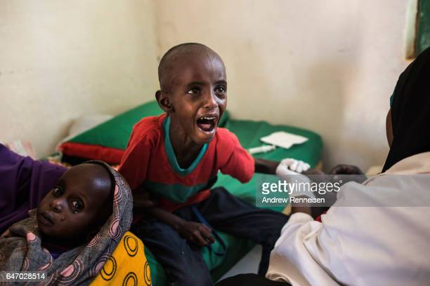 Abdullahi Mohamud cries as a nurse struggles to find a vein for an injection at a government run health clinic on February 25 2017 in Shada Somalia...
