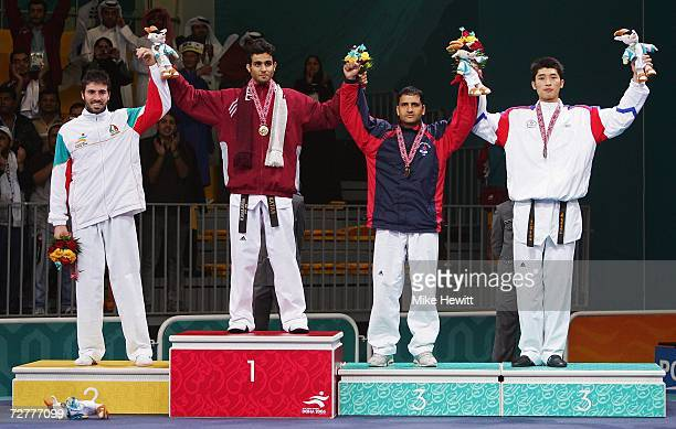 Abdulqader Hikamt A Sarhan of Qatar celebrates winning the gold medal with silver medallist Mehdi Bibak Asl of Islamic Republic of Iran and bronze...