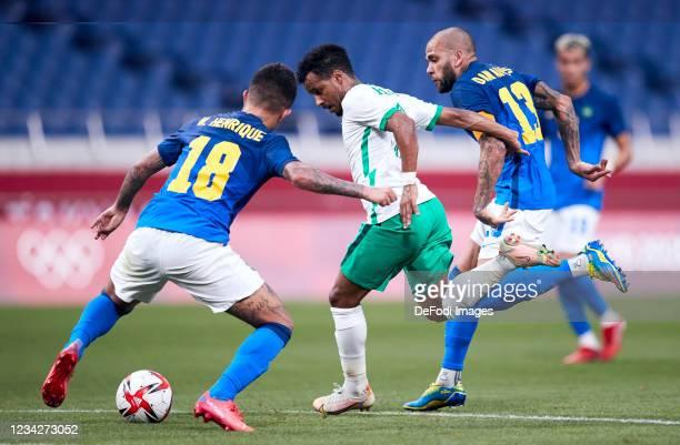 Abdulrahman Ghareeb of Saudi Arabia, Dani Alvez of Brazil and Henrique Matheus of Brazil battle for the ball during the Men's Group D match between...
