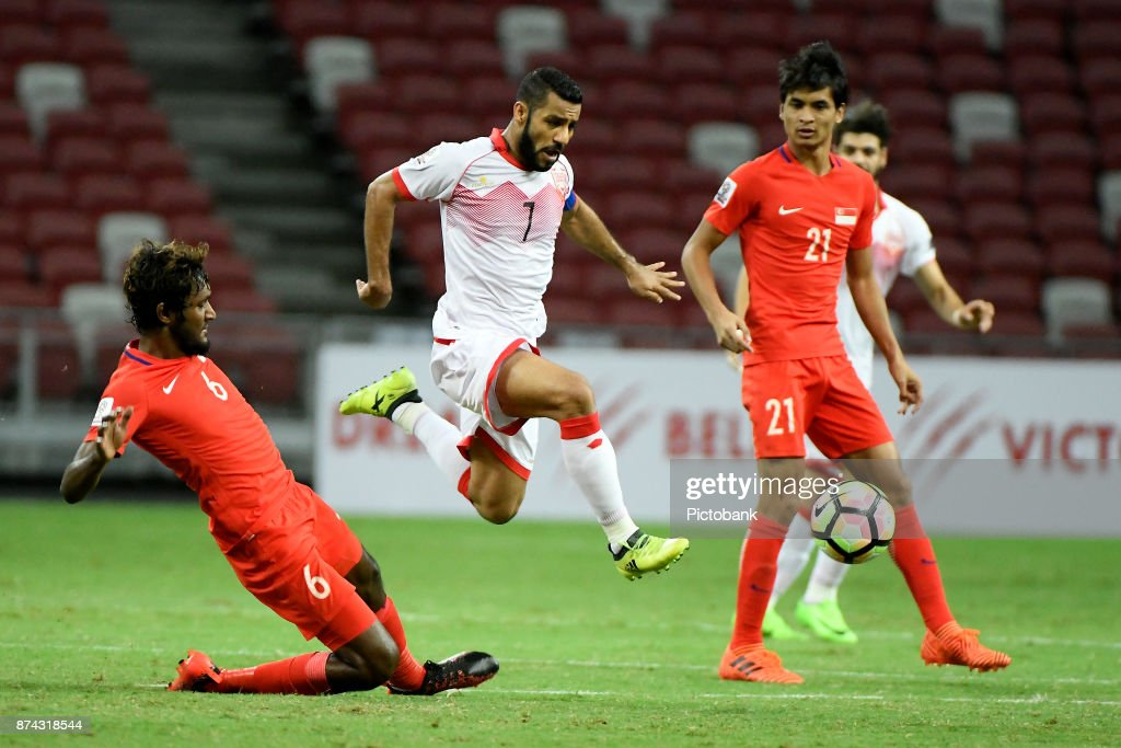 Abdulwahab Ali Alsafi of Bahrain runs with the ball while Madhu Mohana of Singapore (L) falls during the Asian Cup Qualifier match between Singapore and Bahrain at the Singapore Sports Hub on November 14, 2017, in Singapore, Singapore.
