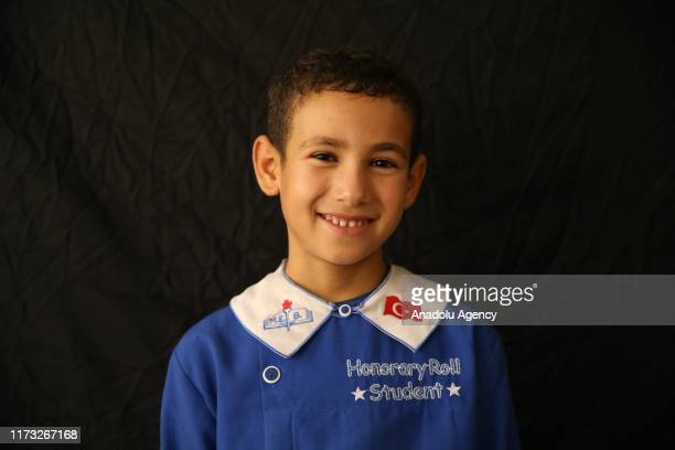 Abdurrahman Ah Ahmar, an eight year-old Syrian boy from Idlib who wants to become a doctor, poses for a photo with a school uniform in Reyhanli...