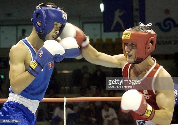 Abdusalom Khasanov of Tajakistan lands a punch on Phyong-Chol Choe of North Korea during the first quarter final in Bantamweight 54 kg category of...