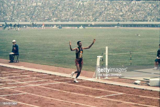 Abebe Bikila of Ethiopia crosses the finishing tape as top in the Men's Marathon during the Tokyo Olympic at the National Stadium on October 21, 1964...